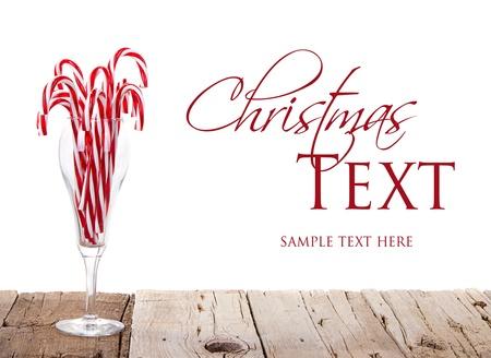 Veel snoep stokken in een glas wijn op een houten plank met een geà ¯ soleerde witte achtergrond