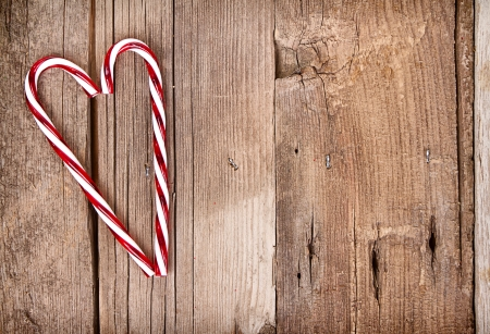Candy canes in a heart shape on a wooden background photo