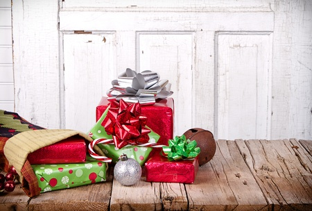 Christmas presents spilling out of a stocking on wooden plank with antique door panel background Foto de archivo