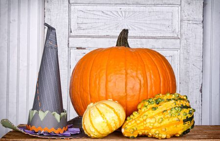 Pumpkins, gourds and a witches hat  with an aged cracked door panel background photo