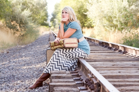 Woman with vintage luggage waiting on railroad tracks photo