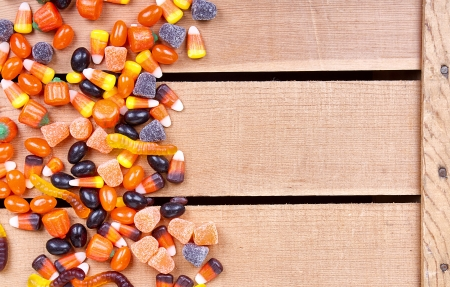 Halloween candy scattered on a wooden crate photo