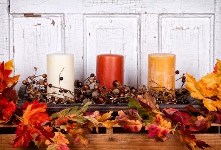 Otoño todavía la vida con velas y hojas con un panel de madera antigua para el fondo Foto de archivo - 15911795