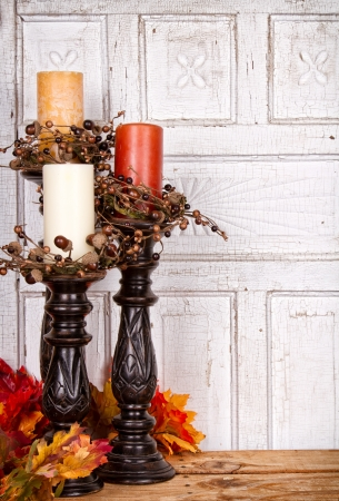 Autumn still life with candles and leaves with an antique wood panel for background photo