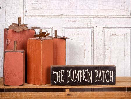 Wooden pumpkins autumn still life with sign and antique panel background Stock Photo