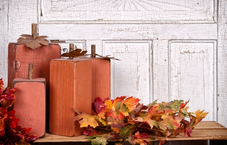 Wooden pumpkins autumn still life with leaves and antique panel background