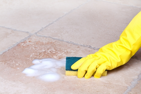 bathroom tiles: gloved hand cleaning tile with sponge Stock Photo