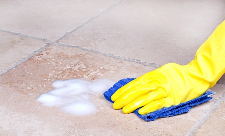 gloved hand cleaning tile with cloth or rag photo