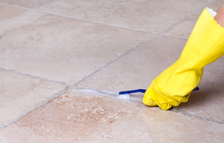 gloved hand cleaning tile grout with toothbrush Archivio Fotografico