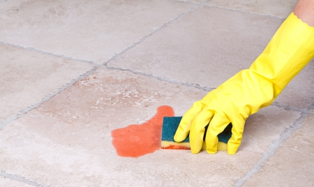 Cleaning up juice spill  on tile floor with sponge photo