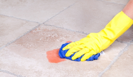 Cleaning up juice spill  on tile floor with cloth photo