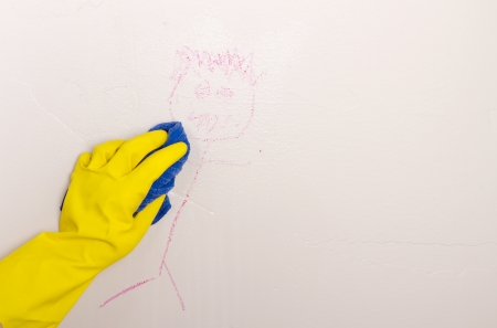 Gloved hand, cleaning crayon off wall with cloth