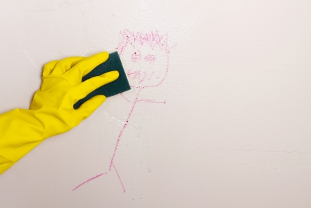 Gloved hand, cleaning crayon off wall with sponge