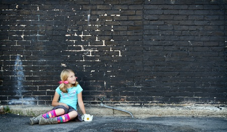 Girl sitting on ground holding flowers next to brick wall  photo