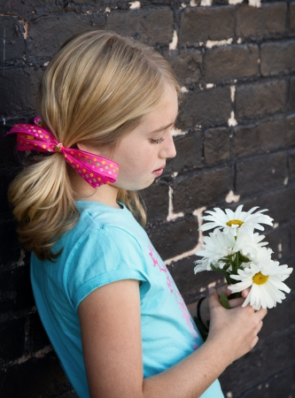 Close up of teen holding flowers by brick wall photo