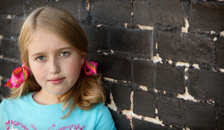 Close up of teen or child by brick wall photo
