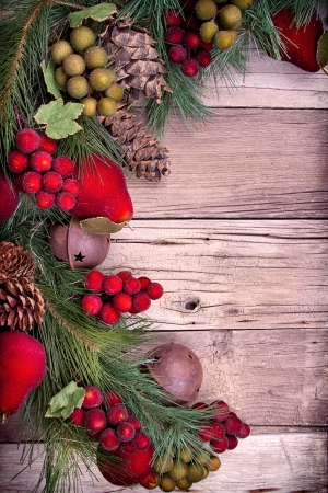 decoration: Christmas decorative fruit and pine branches on wooden background
