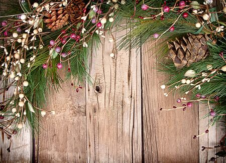 Christmas berries and pine branches on wooden background photo