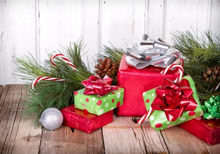 Christmas Presents and Ornaments on Wooden Background With Pine Branches