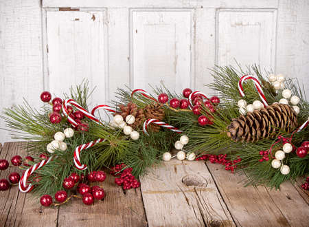 Christmas berries, Candy canes and pine branches on wooden background photo