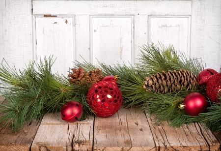 motivos navideños: Adornos de Navidad y ramas de pino sobre fondo de madera
