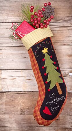 Handmade Christmas stocking stuffed with presents and decorations on wooden background photo