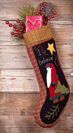 Handmade Christmas stocking stuffed with presents and decorations on wooden background Stock Photo - 15911752