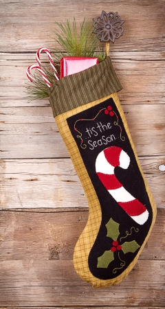 Handmade Christmas stocking stuffed with presents and decorations on wooden background Stock Photo