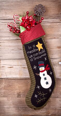 christmas sock: Handmade Christmas stocking stuffed with presents and decorations on wooden background Stock Photo