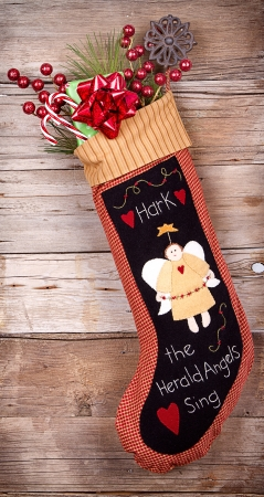 retro christmas: Handmade Christmas stocking stuffed with presents and decorations on wooden background Stock Photo
