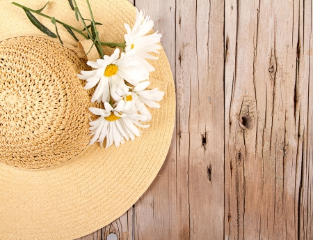 Sun hat and daisies on wooden plank photo