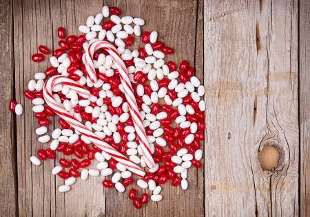 Christmas candy, jelly beans and candycanes, on wooden background photo