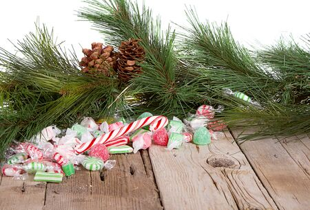 Christmas candy on a wooden background with pine branches photo