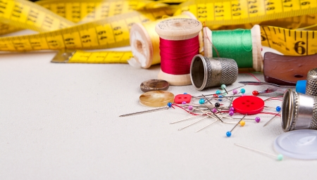 Sewing supplies, measuring tape, thread, pins, buttons and thimbles