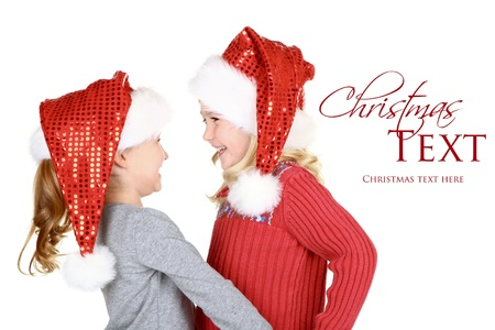 Two Children wearing Santa hats laughing on isolated white background photo