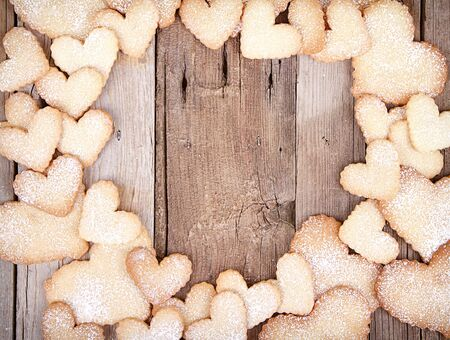 shaped: Heart shaped sugar cookies stacked framing a wooden background