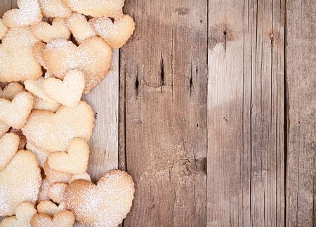 shaped: Heart shaped sugar cookies stacked on wooden background Stock Photo