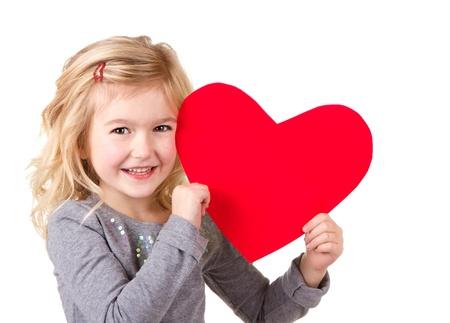 ni�os sosteniendo un cartel: Ni�a que sostiene el coraz�n rojo, primer plano aislado en blanco Foto de archivo