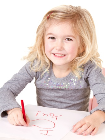 Little girl writting I love you on white paper, isolated on white photo