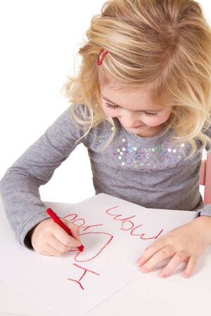 Little girl writting I love you mom, on white paper, isolated on white photo