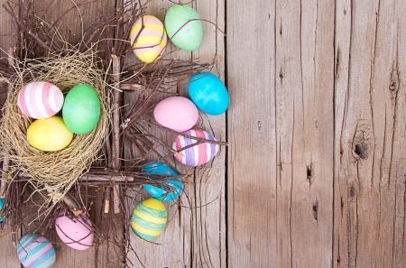 Easter eggs in nest on rustic wooden planks Standard-Bild