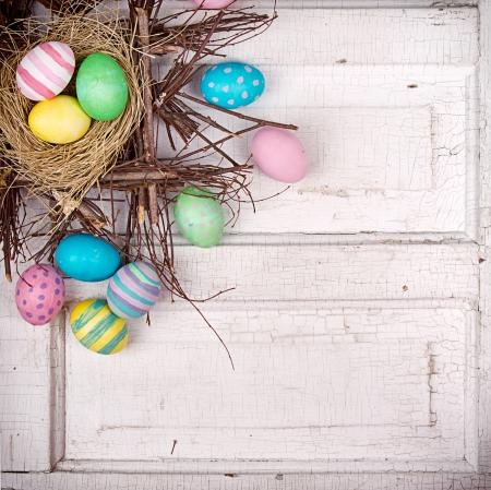 Easter eggs in nest on white antique wooden panel.