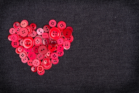 Assorted red buttons in shape of heart on denim fabric background