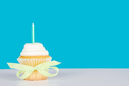 Single vanilla cupcake with green candle and sprinkles on a blue background and white table and bow photo