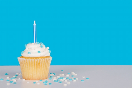 Single vanilla cupcake with blue candle and sprinkles on a blue background and white table photo