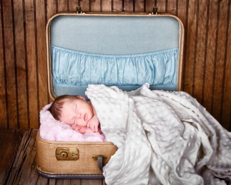 Newborn infant baby sleeping in suitcase