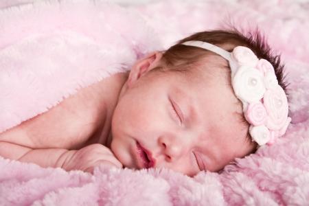Newborn infant girl sleeping on a pink blanket