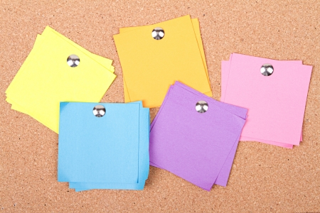 assorted blank sticky notes on a bulletin board photo