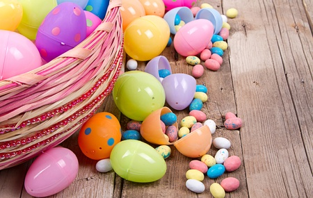 Plastic easter eggs filled with candy in a Easter basket on a wooden background photo