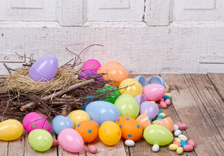 Plastic Easter Eggs By Nest Filled With Candy On A Woode Background Stock Photo